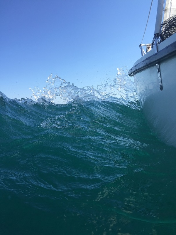 water splashing off sailboat bow